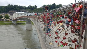 Love Lock Bridge, Salzburg. A love lock or love padlock is a padlock which sweethearts lock to a bridge, fence, gate, or similar public fixture to symbolize Stock Photography