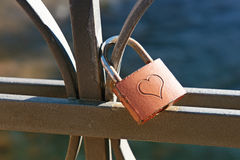 Love lock engraved with a heart. To signify commitment and lifelong love locked on a wrought iron railing or balustrade, a trendy fad by tourists considered an Stock Image