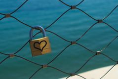 Love lock in front of blue sea. Close-up of a simple metal love lock with a drawing of a heart hanging on a bridge railing in front of the aquamarine sea stock images