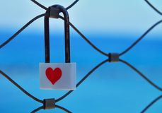 Love lock in front of blue sea. Close-up of a white love lock with a red heart hanging on a bridge railing in front of the bright blue sea stock image