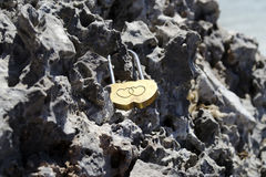 Love lock in stone. Romantic love lock in shape of heart hitched to the rock Royalty Free Stock Photos