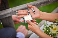 Love Lock. Young brides hand with lock with hearts symbol in it. It is Latvian tradition to lock your love to the birdge and throw the key in the river Stock Images