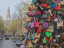 Love locks on Amsterdam bridge. Hundreds of padlocks (called love locks) on a bridge crossing a canal (so called gracht) in Amsterdam, Netherlands. People close Royalty Free Stock Image