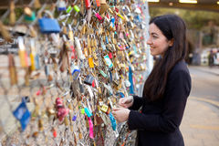 Love locks. Girl looking at love locks attached to a fence Stock Image
