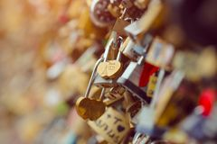 Love locks in Paris France bridge. Symbol of friendship and romance. Close-up macro shot with selective focus on one lock Stock Photography