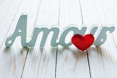 Love, love. red heart and the word amour on a white wooden background.  Royalty Free Stock Image
