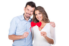 Love. Loving couple. Beautiful young loving couple holding paper hearts and smiling while isolated on white Royalty Free Stock Photos