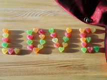 Love made of fruit candy and wedding rings Royalty Free Stock Photos