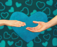 Love. Male hand reaches for the female hand against hearts painted background Stock Photos