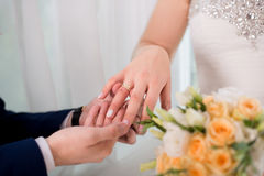Love and marriage. Wedding ceremony up of groom putting golden ring on the bride`s finger. Love and marriage. Wedding ceremony. Close up of groom putting golden Royalty Free Stock Images