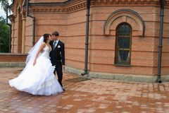 Love meeting. Bride and groom meet at a church court Royalty Free Stock Image