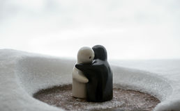 Love melts the ice Valentine `s day concept. F girl and a boy dolls hugs each other, standing on the white snow with blurred backg Royalty Free Stock Images