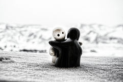 Love melts the ice Valentine `s day concept. F girl and a boy dolls hugs each other, standing on the white snow with blurred backg Stock Photography