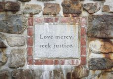 Love Mercy Seek Justice Inscription. A stone plaque inset in in a rough Limestone wall surrounded by brick Stock Photography