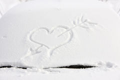 Love message. Arrow and heart in the snow Stock Photos