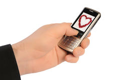 Love message. Hand of man holds a mobile telephone with a love message on the screen Stock Photos