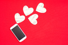 Love message. A cell phone with paper hearts making a love message Royalty Free Stock Photo