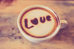 Love message on coffee cup on wood. En background with vintage colour effect. Still life Royalty Free Stock Photo