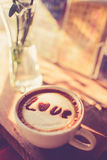 Love message on coffee cup on wood. En background with vintage colour effect. Still life Royalty Free Stock Photos