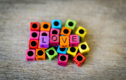 Love message cubes. Colorful love message cubes on wooden background Royalty Free Stock Images