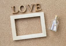 Love message, message bottle and wooden frame with love text. On corkboard background Stock Photos