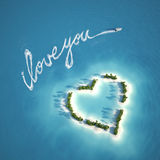 Love message on the water. Boat writing a love message with the trail on the water near a heart shape island ideal for valentines post card Royalty Free Stock Photos