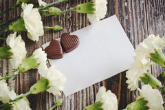 Love message. White carnations, chocolates and white sheet of paper. love letter Royalty Free Stock Photos