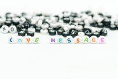 Love message written with colored letters and black and white letter in background on white concept photo royalty free stock photo