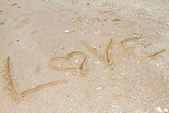Love message written in sand Stock Images