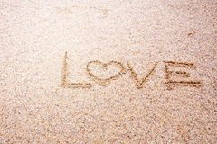 Love message written in sand, Sign Love on sand on beach.  Royalty Free Stock Photos