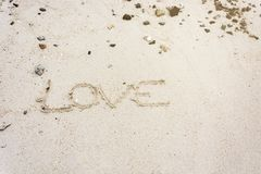 Love message written in sand, Sign Love on sand. On beach Royalty Free Stock Image