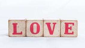Love message written in wooden blocks. On white background Royalty Free Stock Photo