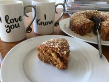 Love messages on coffee mugs. Romantic love messages on two coffee mugs beside fresh backed cake stock photos
