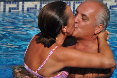 Love in middle age. A middle age couple is enjoying their love in a swimming pool at Summer Royalty Free Stock Photo
