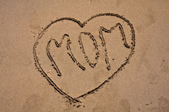 Love mom on the beach. Love mom hand draw on the sand on the beach Royalty Free Stock Images