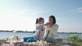 Love for mom, little girl feeds mum during relaxation on family picnic on lawn near lough in weather. Love for mom, little girl feeds mum during relaxation on stock footage