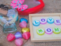 Love mom spelled with colorful alphabet blocks. And a red heart isolated on wooden board and  sack - Mothers Day Royalty Free Stock Photos
