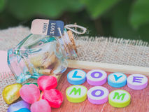 Love mom spelled with colorful alphabet blocks. And a red heart isolated on wooden board and  sack - Mothers Day Stock Photo
