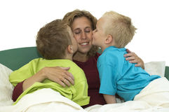 We Love Mommy. Mother and two sons lying happy in bed, kissing mommy Royalty Free Stock Photos