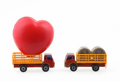 Love and money. Love vs money toy trucks loaded with heart and coins facing each other isolated on white with clipping path Stock Images