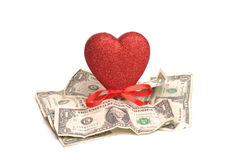 Love Of Money. A photograph of a heart and us dollar notes, shot in studio against a white background Stock Photo