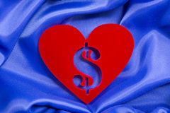 Love money. Red heart shape with dollar sign inside of a plexiglas material on a blue silk background royalty free stock photography