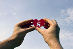 Love money. Hands holding red heart shape with a dollar sign inside against the sky with clouds royalty free stock photo