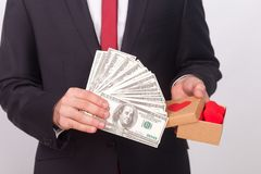 Love or money. Which is better, proposes man in suit. Indoor, studio shot, on gray background royalty free stock photos