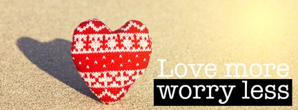 Love more worry less. Inspirational motivation quote with phrase Love more worry less, Red Heart on a sand beach background Stock Photo