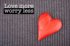 Love more worry less. Inspirational motivation quote with phrase Love more worry less, Red Wooden Heart on Knitted Background Stock Photography