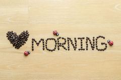 Love morning. Coffee beans  used to spell love morning on wooden background Royalty Free Stock Images
