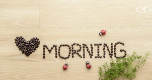 Love morning. Coffee beans  used to spell love morning on wooden background Royalty Free Stock Image