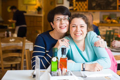 Love of mother and daughter. Happy women in a nice cafe with copy space on blurred background. Aged woman and her adult Royalty Free Stock Images