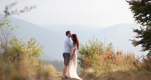 Love in the mountains. Man hugs woman from behind tender and kisses her watching sunset over the mountains on a hill.  stock video